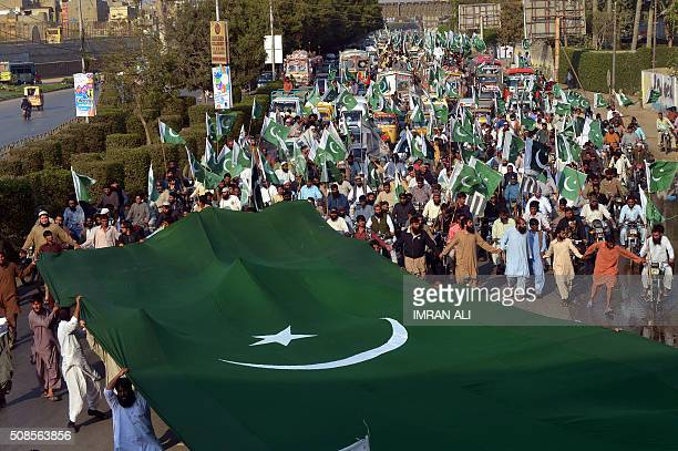 Pakistani supporters of the banned organisation JamaatudDawa carry national flags as they march during a protest to mark Kashmir Solidarity Day in...