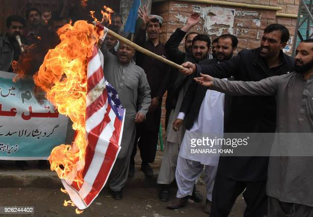 Pakistani supporters of the JamaateIslami organisation burn a US flag during a protest against the ongoing conflict in Syria during a protest in...