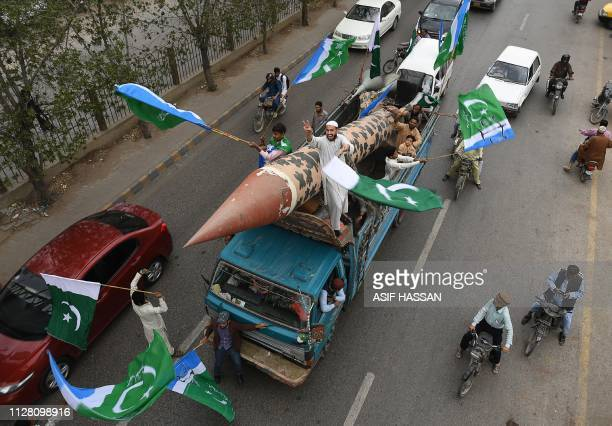 Pakistani supporters of the JamaateIslami party march along with a replica of a missile during an antiIndian protest rally in Karachi on February 28...