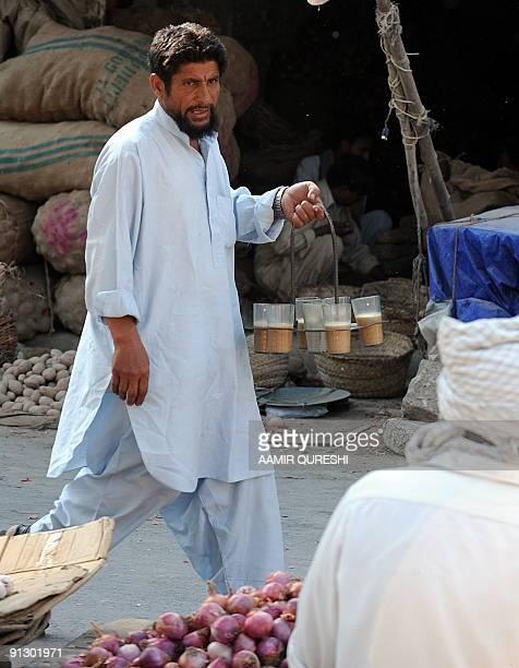 A Pakistani tea vendor offers tea to customers as he walks through a wholesale market in Rawalpindi on September 30 2009 Pakistan's central bank has...