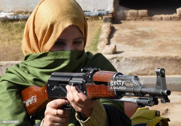 A Pakistani teacher handles an AK47 assault rifle during a weapons training session for school college and university teachers at a police training...