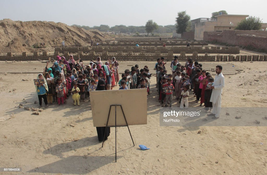 Pakistani teacher teaches students at bricks kiln open air school on the eve of World Teachers Day in LahoreOctober 052017World Teachers` Day held...
