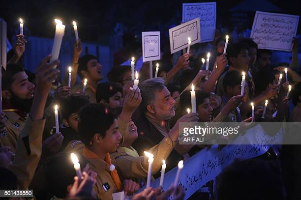 Pakistani teachers and students hold burning candles during a vigil to pay tribute to the victims of the Peshawar school massacre of December 16 the...