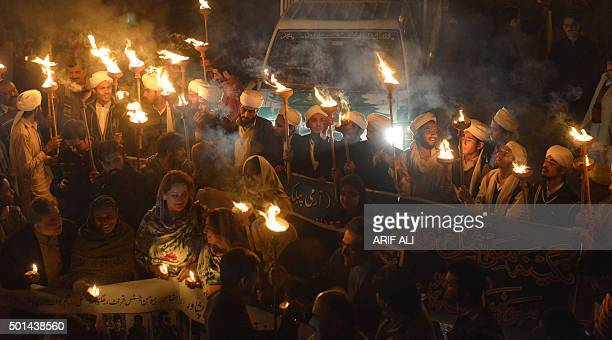 Pakistani teachers and students hold burning torches during a vigil to pay tribute to the victims of the Peshawar school massacre of December 16 the...