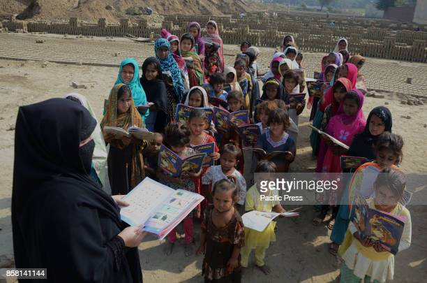 Pakistani teachers teaching their class in a government funded Non Formal Basic Education School at a bricks kiln in the outskirts of Lahore on...