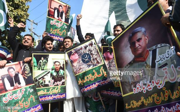 Pakistani traders shout slogans and carry posters with the image of Pakistani Army Chief General Qamar Javed Bajwa during an antiIndia protest in...