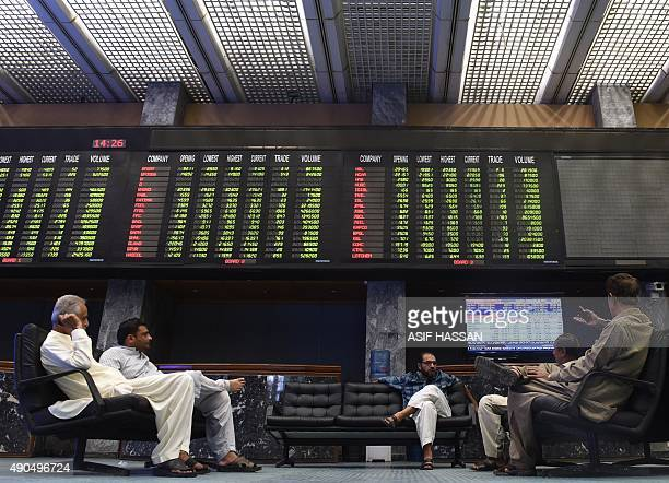 Pakistani traders sit below a board displaying the latest share prices during trading at The Karachi Stock Exchange in Karachi on September 29 2015...