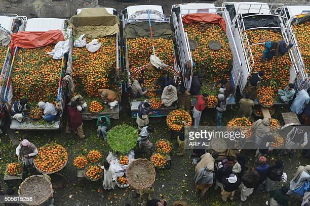 TOPSHOT Pakistani traders wait for customers at a fruit and vegetable market in Lahore on January 19 2016 AFP PHOTO / ARIF ALI / AFP / Arif Ali