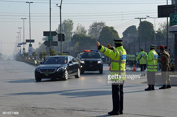 A Pakistani traffic police officer directs government vechiles on their way to attend a ceremony to mark the first anniversary of the school massacre...
