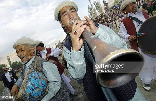 Pakistani tribesmen play traditional musical instruments during a festival to celebrate the golden jubilee of the first ascent of K2 the second...