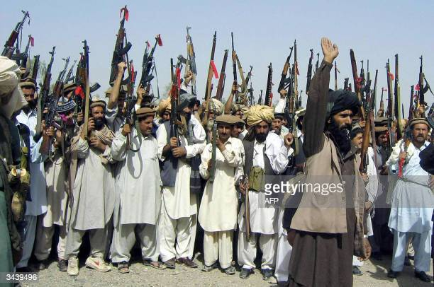 Pakistani tribesmen raise their red-ribbon tied AK-47 assualt rifles during a meeting in Wana, the main town in the South Waziristan tribal territory...