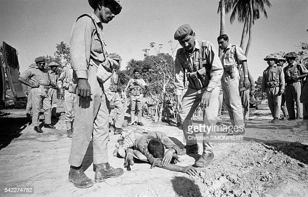 Pakistani troops observe the body of an Indian officer who was killed in fighting near Jessore during the war for Bangladeshi independence