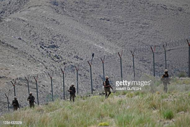 Pakistani troops patrol along Pakistan-Afghanistan border fence at Big Ben post in the Khyber district of the Khyber Pakhtunkhwa province on August...