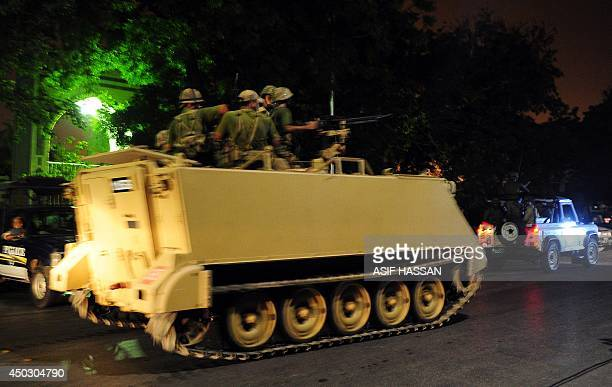 Pakistani troops take position with an armored vehicle at he Karachi airport terminal after the militants' assault in Karachi late on June 8 2014...