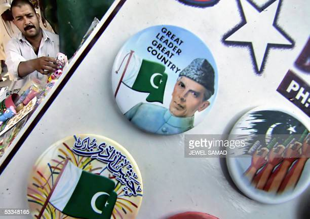 Pakistani vendor arranges his road-side stall siting behind a display of badges featuring a picture of country's founder Mohammad Ali Jinnah and...