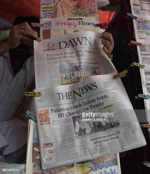 A Pakistani vendor arranges morning newspapers featuring front page coverage of Pakistan's victory against India in the ICC Champions Trophy final...