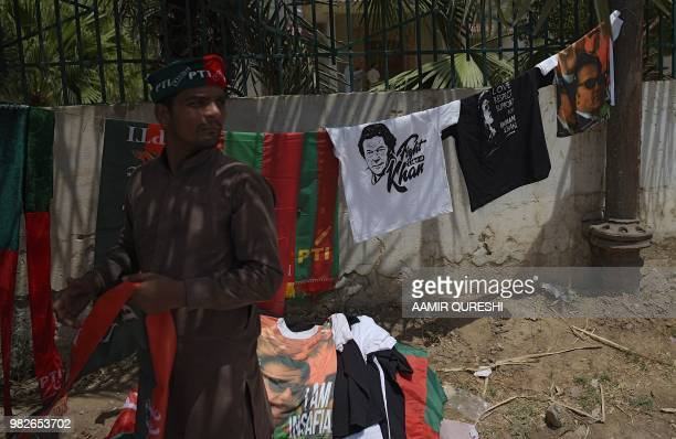 Pakistani vendor arranges T-shirts featuring images of former cricket-turned politician Imran Khan neat the venue of an election campaign meeting by...