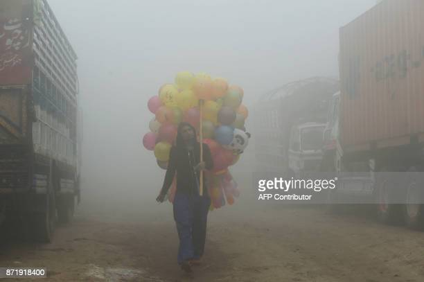 Pakistani vendor carries baloons on a street amid heavy smog in Lahore on November 9 2017 Flights were cancelled school times pushed back and...