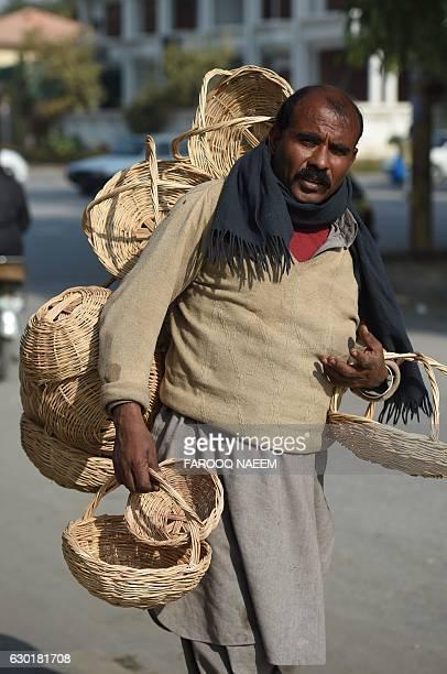A Pakistani vendor carries handmade baskets for sale on a street in Rawalpindi on December 18 2016 / AFP / FAROOQ NAEEM