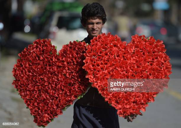 A Pakistani vendor carries heartshaped bouquets for sale ahead of Valentine's Day along a street in Islamabad on February 13 2017 / AFP PHOTO / AAMIR...