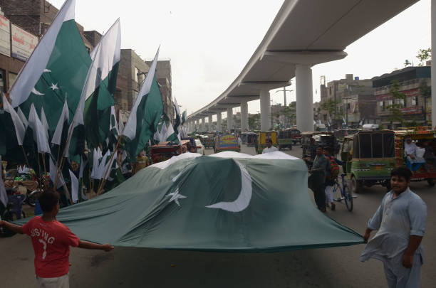 Pakistani vendor displays a large size National flag in connection with 71st Independence day celebrations in Lahore Streets nationwide brimmed with..