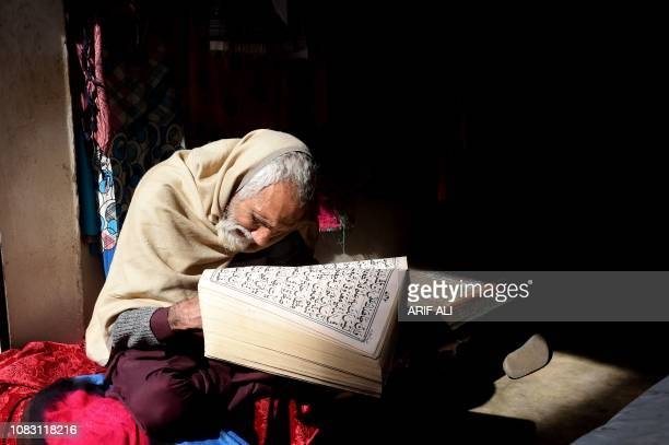 Pakistani vendor of women garments reads the Koran while waiting for customers at his shop in Lahore on January 15 2019