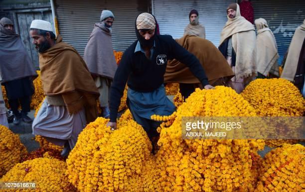 A Pakistani vendor places arranges marigold flower bundles at a flower market on the outskirts of Peshawar on December 15 2018