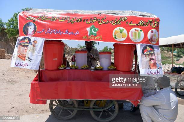 A Pakistani vendor prepares lemon drinks for customers at his roadside stall on which hang posters with images of Pakistan's army chief General Qamar...