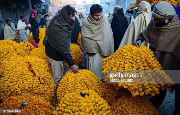 A Pakistani vendor sells marigold flower bundles at a flower market on the outskirts of Peshawar on December 15 2018