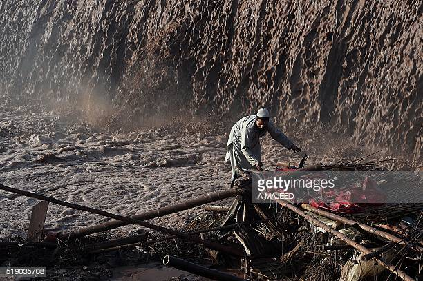 A Pakistani vendor tries to salvage materials after flood water destroyed his shop following heavy rain on the outskirts of Peshawar on April 4 2016...