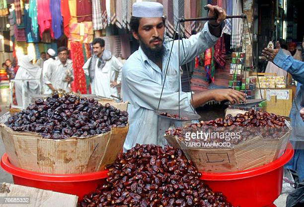 A Pakistani vendor weighs dates for a customer in Peshawar 12 September 2007 ahead of the start of holy fasting month of Ramadan Ramadan starts in...