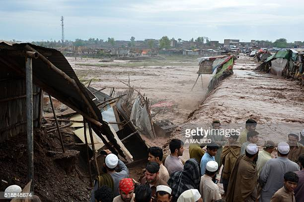 Pakistani vendors and residents gather beside flood waters rushing through a market area on the outskirts of Peshawar on April 3 2016 Heavy rains...