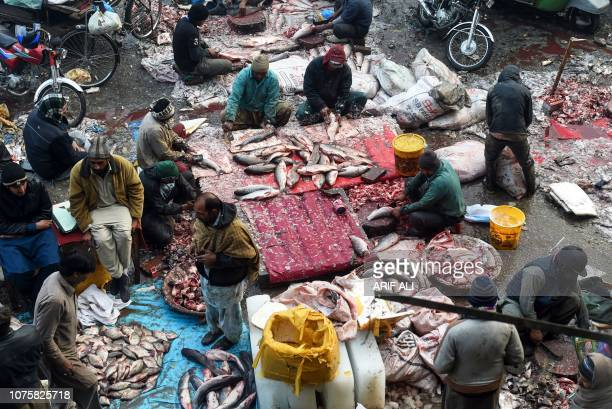 Pakistani vendors prepare fish to be sold at a fish market in Lahore on December 30 2018