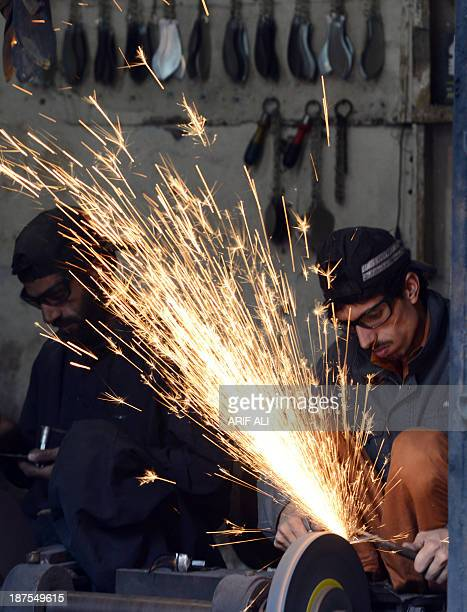 Pakistani vendors sharpen knives which are hung from chains and used in a ritual of self flagellation by Shiite Muslims for Ashura at a shop in...