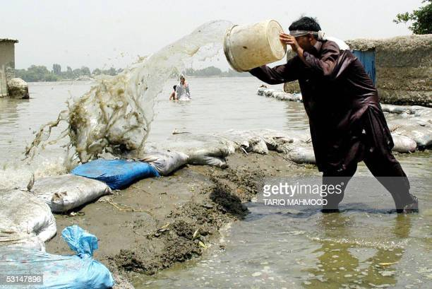 Pakistani villager bales out water from a temporary embankment he made to protect his house from floodwater in Landi Daud Zai village some 30...