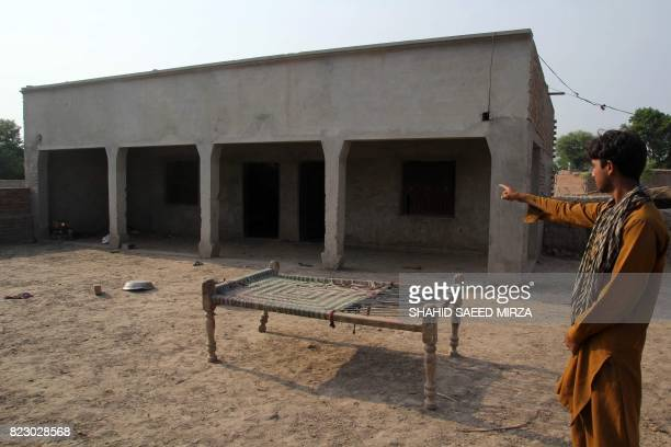 A Pakistani villager poses as he points to a house where a teenage girl was raped in the neighbourhood of Raja Ram in Muzaffarabad a suburb of the...