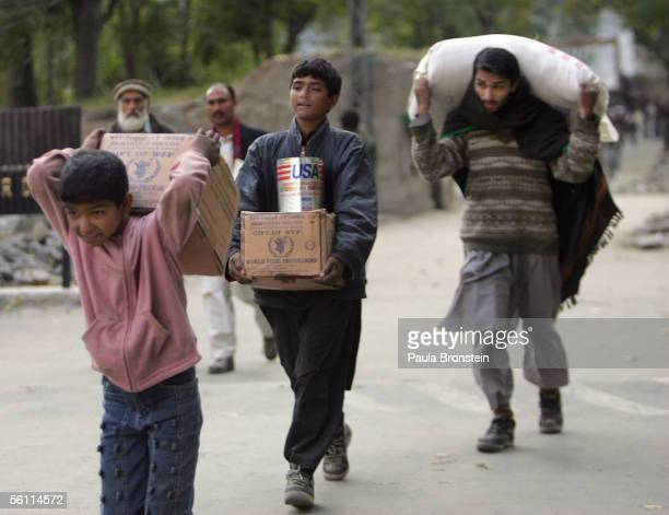 Pakistani villagers carry 75 kg boxes of Wolrd Food Program high energy biscuits from a helicopter November 6 2005 in Chham Jhelum Valley in Pakistan...