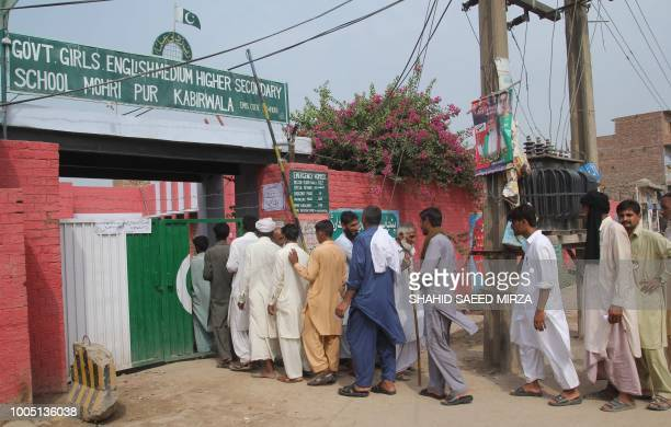 Pakistani villagers enter an a polling station to cast their vote during general election in Mohri Pur some 60 kilometres from the central Pakistan...