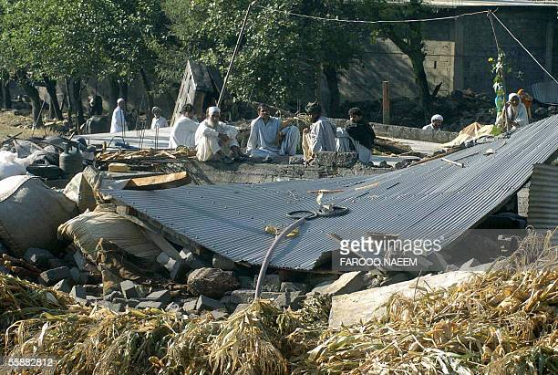 Pakistani villagers sit next to their collapsed house as they wait for relief goods in the earthquake worst hit village of Balakot in Pakistan's...