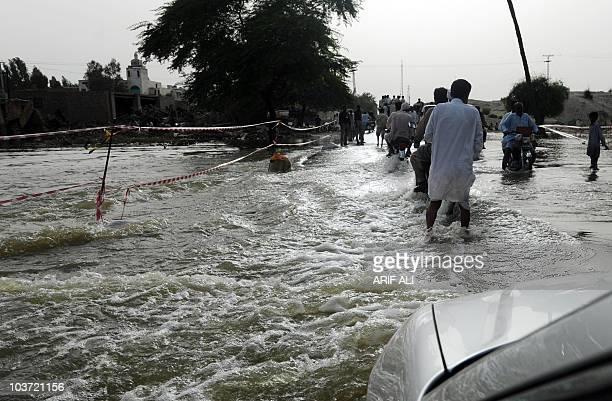 Pakistani villagers wade through floodwaters in Karam Dad Qureshi village in Dera Ghazi Khan district on August 27 2010 Pakistan ordered 300000...
