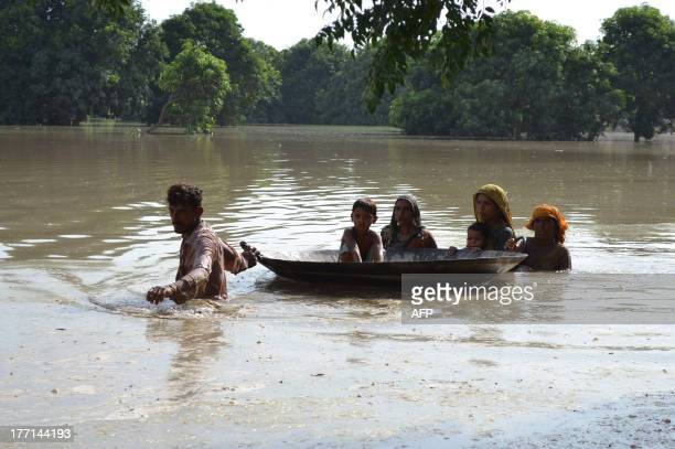 Pakistani villagers wade through floodwaters on the outskirts of Multan on August 21 2013 Heavy monsoon rains triggering floods have affected nearly...