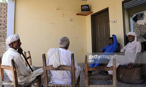 Pakistani villagers watch breaking news on the Indian court verdict against alleged surviving gunman of the Mumbai massacre Mohammed Ajmal Amir Kasab...