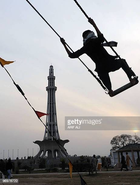 A Pakistani visitor swings in front of the MinariPakistan monument in Lahore on February 12 2010 MinariPakistan is one of the most important national...