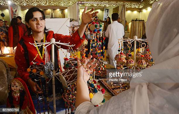 Pakistani visitors taking interest on items displayed during Arts and Crafts Fair exhibition organized by Daachi Foundation at a local hotel in...
