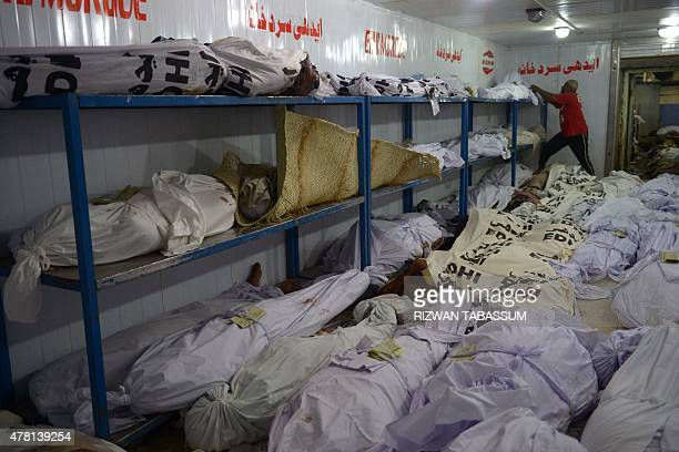 A Pakistani volunteer checks identification paper of a heatstroke victim at a cold storage of the Edhi morgue in Karachi on June 23 2015 The death...
