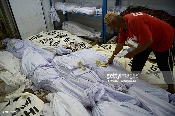 A Pakistani volunteer checks identification papers of a heatstroke victim at a cold storage of the Edhi morgue in Karachi on June 23 2015 The death...