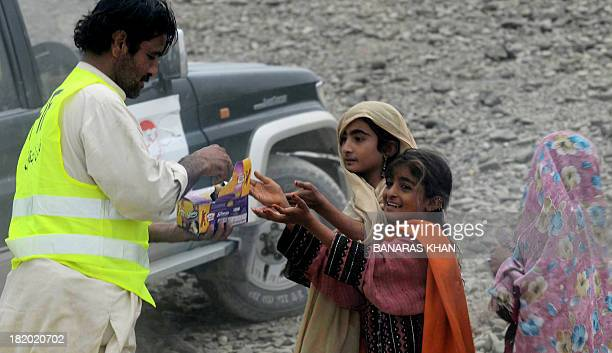 A Pakistani volunteer distributes biscuit to earthquake survivor girls near their collapsed mud houses in the earthquakedevastated district of Awaran...