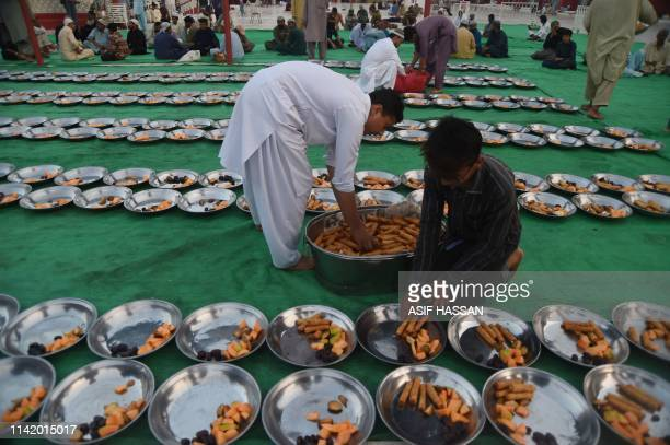 A Pakistani volunteer prepares Iftar food for Muslim devotees prior to breaking their fast on the first day of the holy month of Ramadan at a mosque...