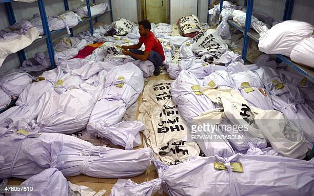 A Pakistani volunteer puts a identification paper onto a body of a heatwave victim as other dead bodies are seen in the the cold storage of the Edhi...