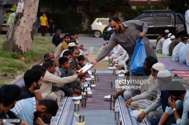A Pakistani volunteer serves Iftar food to Muslims breaking their fast during the holy month of Ramadan in Islamabad on May 21 2018 Muslims...